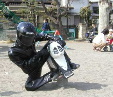 man in playground in leathers and helmet on toy motorbike